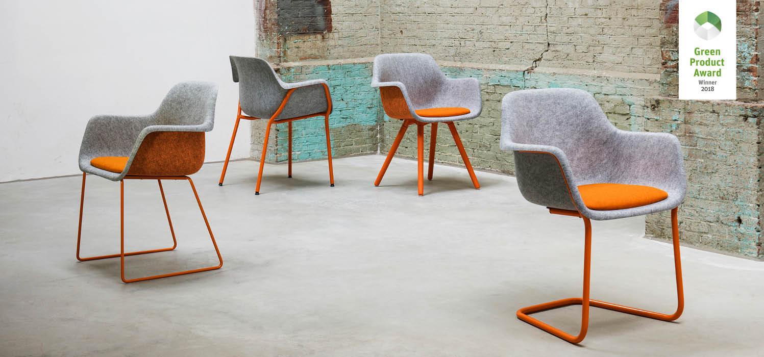stoelen staan door elkaar in een lege ruimte met een stenen muur