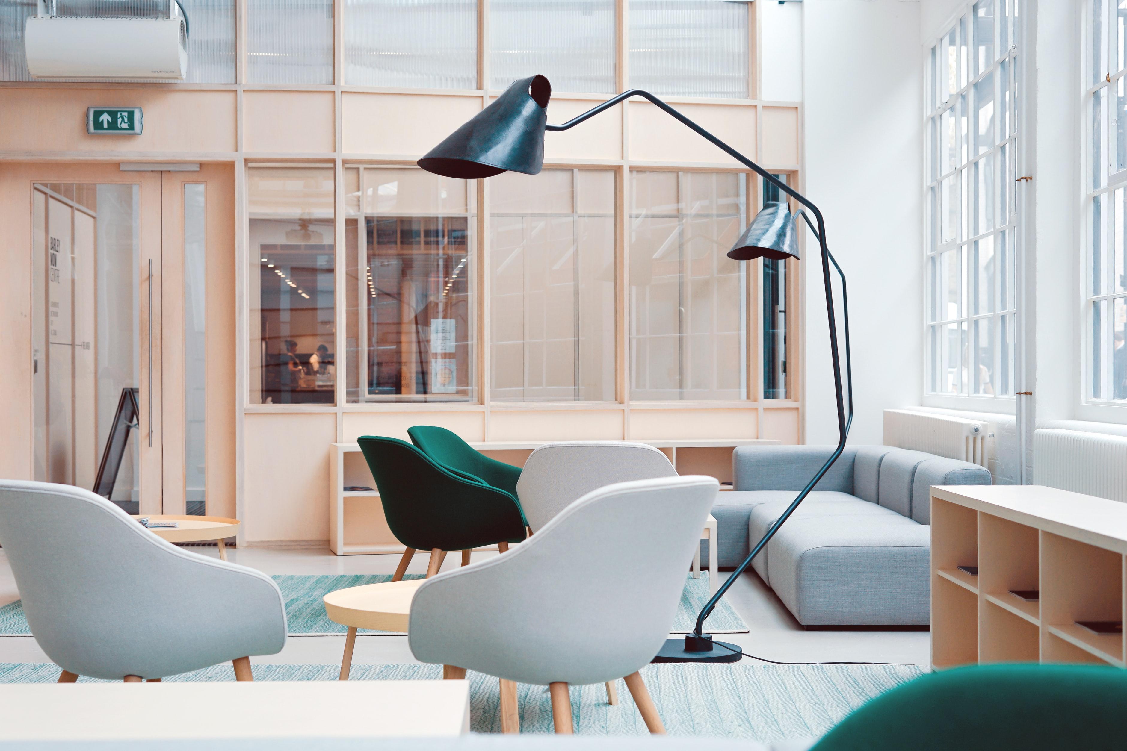 lichte ruimte met stoffen stoelen, een bank en twee grote staande lampen