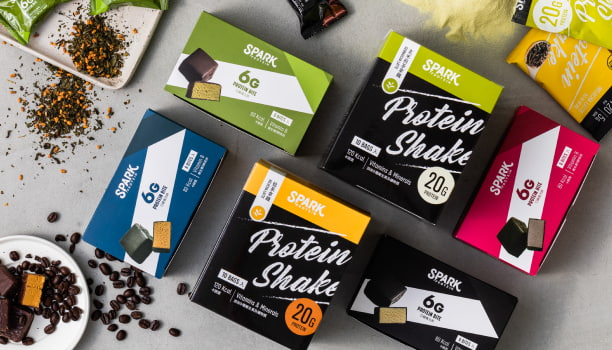 Product flat lay with boxes of Spark protein shake and protein bites