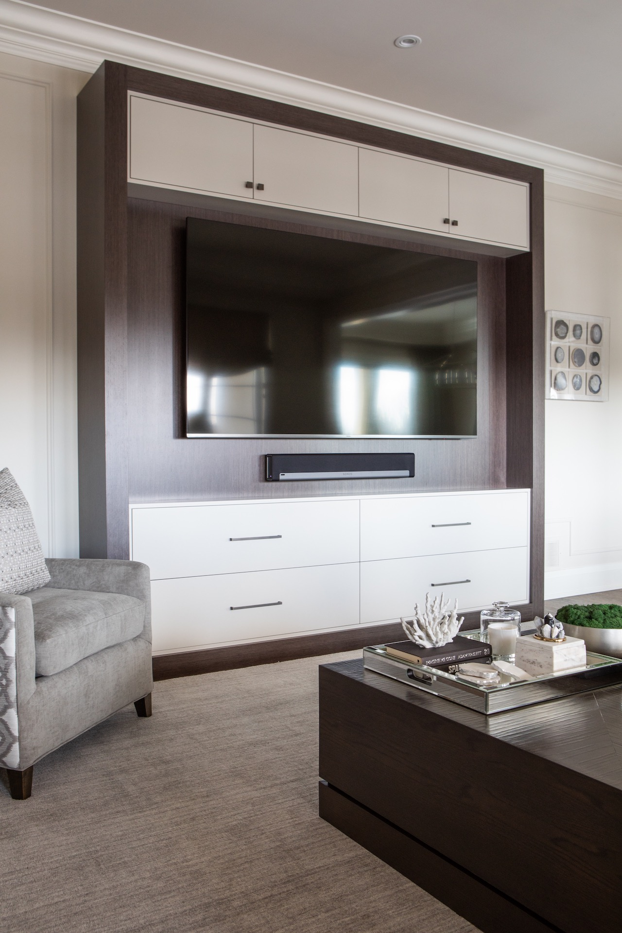 TV mounted on wall in wood cabinet