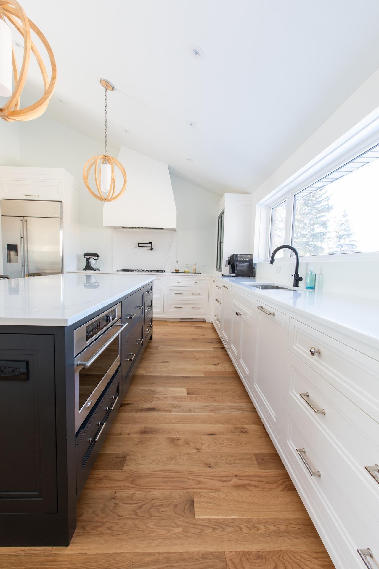 Wood floor, white cabinets blue island