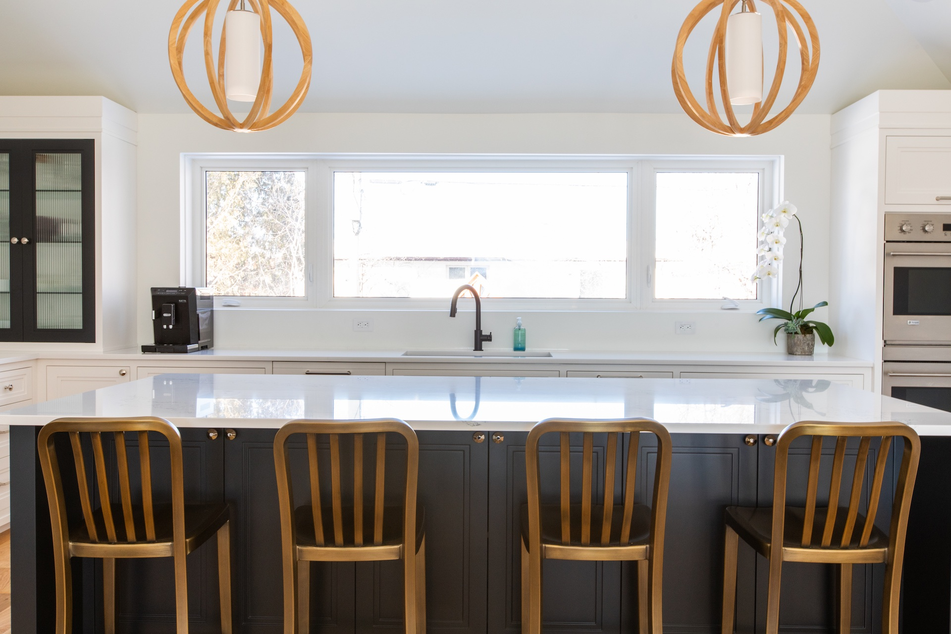 Kitchen with blue island with gold chairs