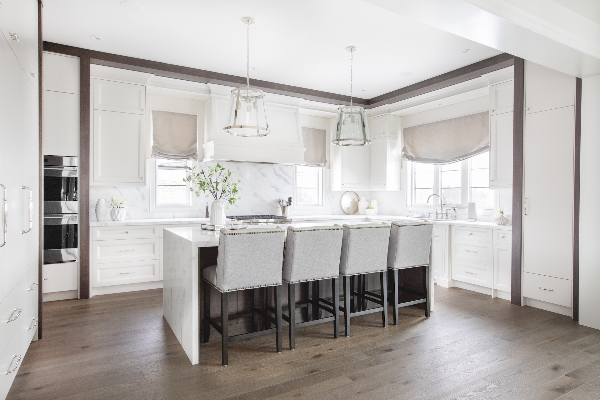 White kitchen with wood floors and bar stools