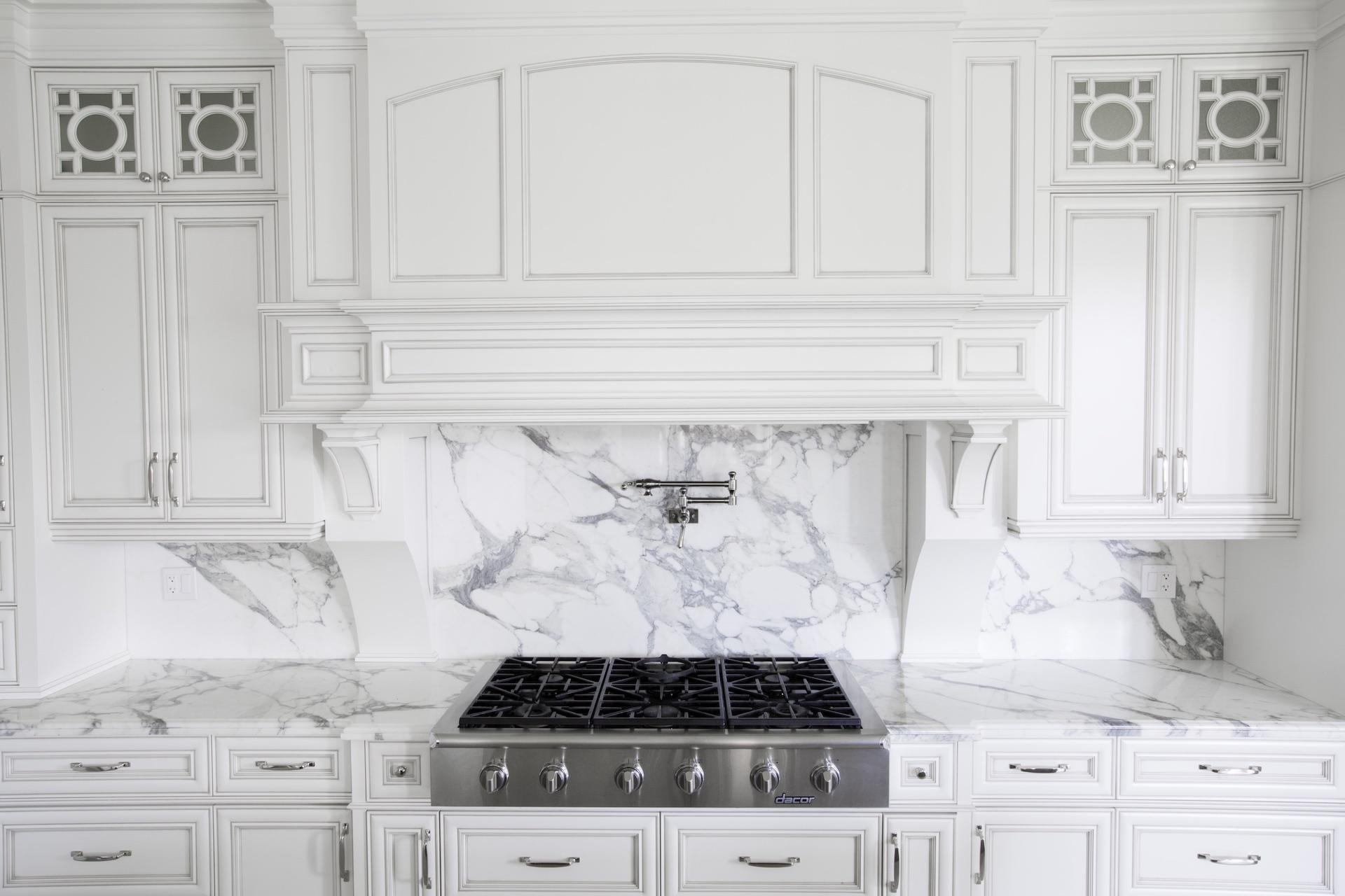 white kitchen cabinets, stove and marble backsplash