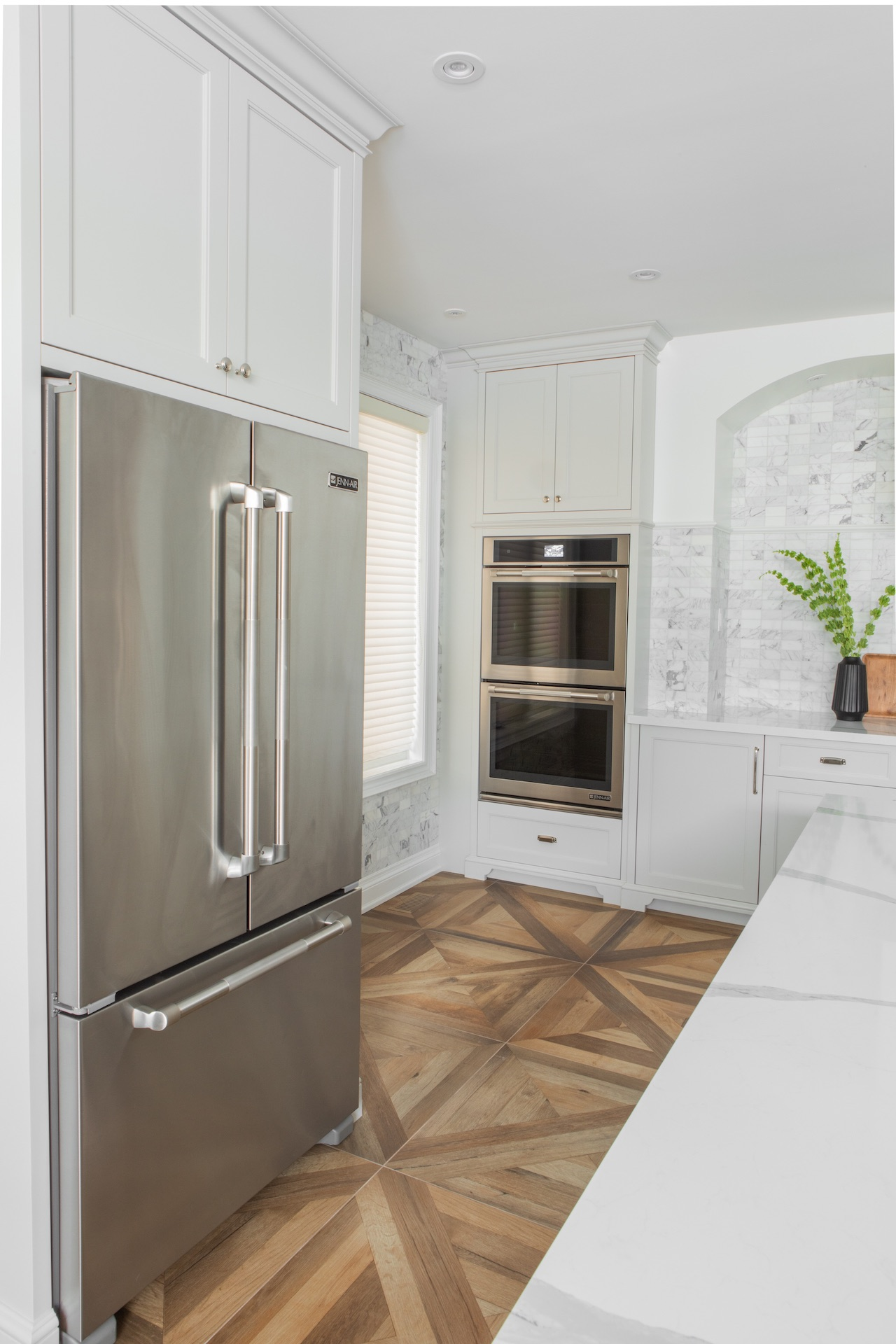 white kitchen with wood floor and silver fridge