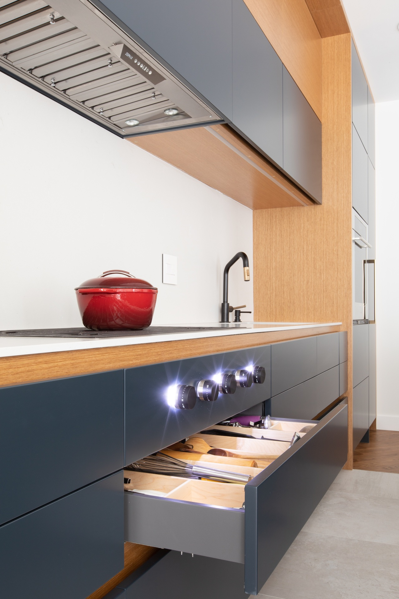 Natural wood and blue kitchen with drawer open and oven