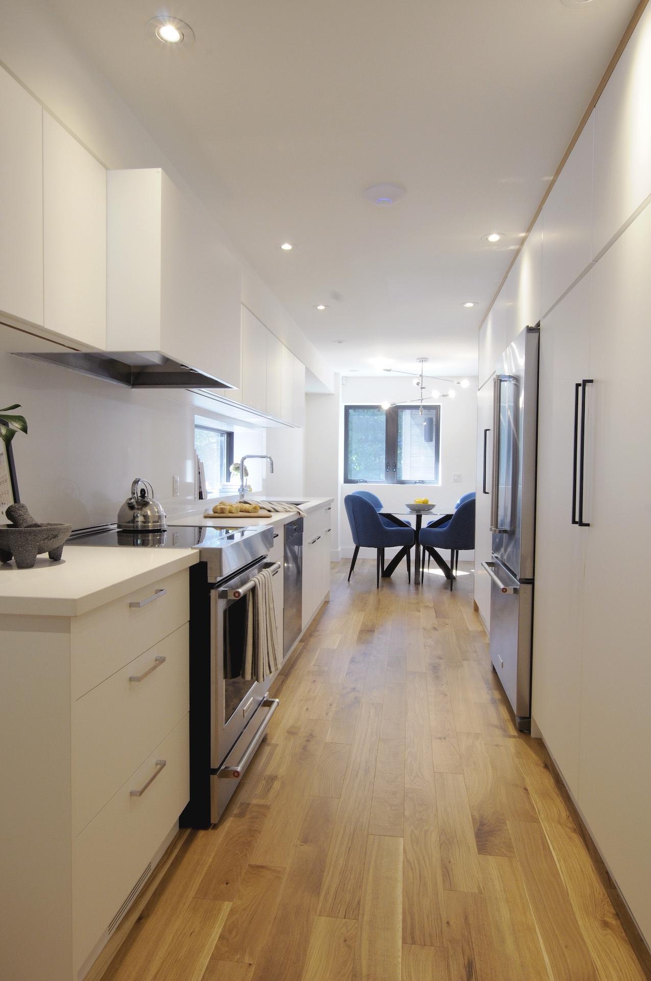 light wood floor and white kitchen