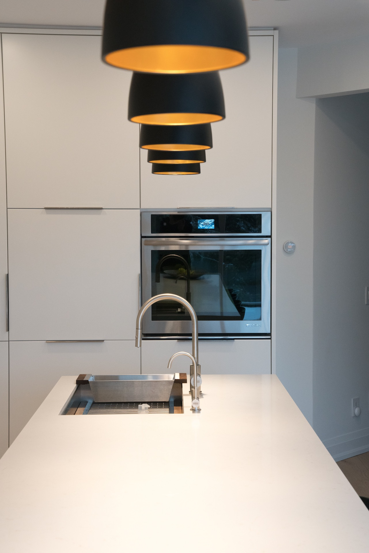 kitchen island with sink, black lights and oven in wall