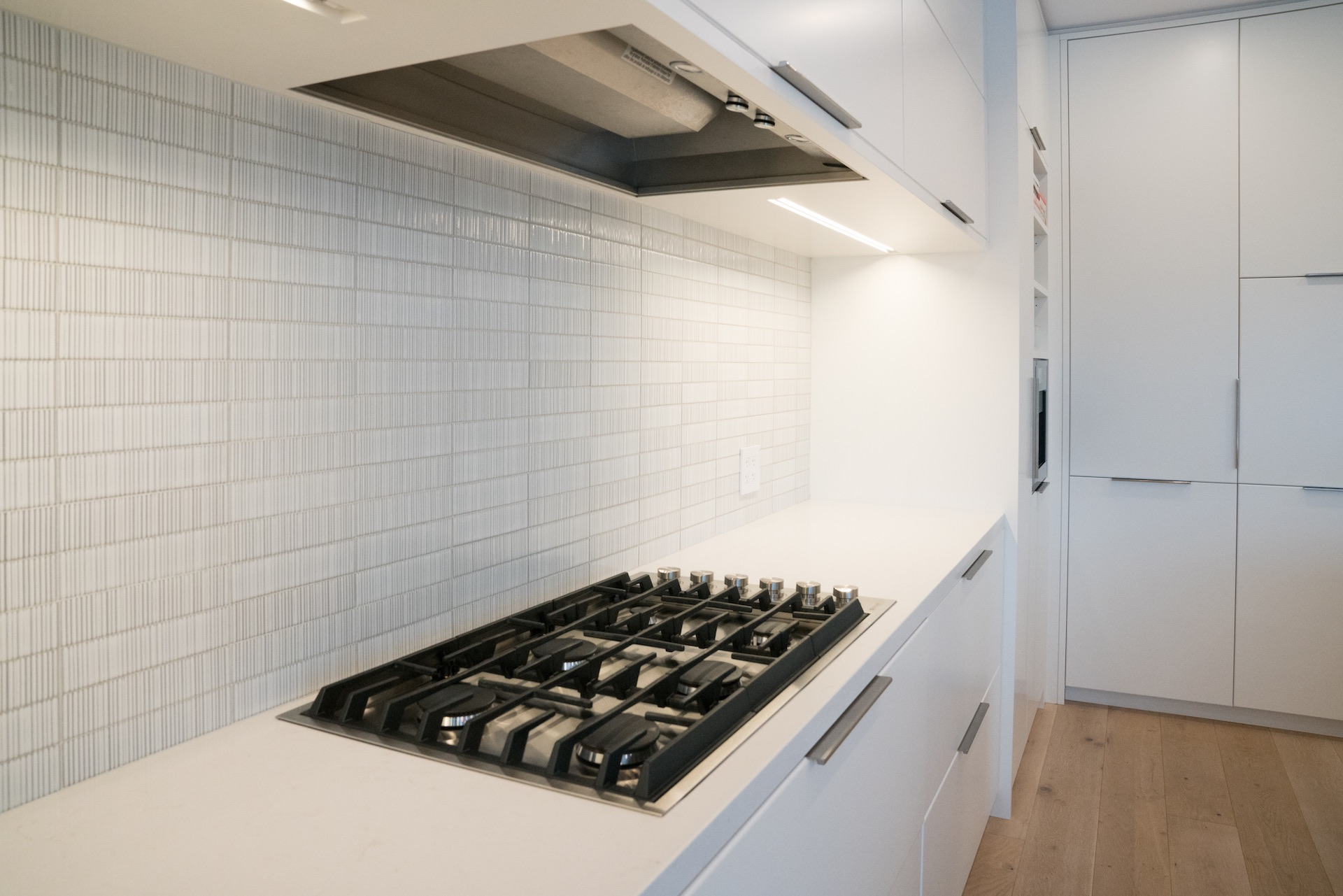 white counter with black grill stove and hood fan