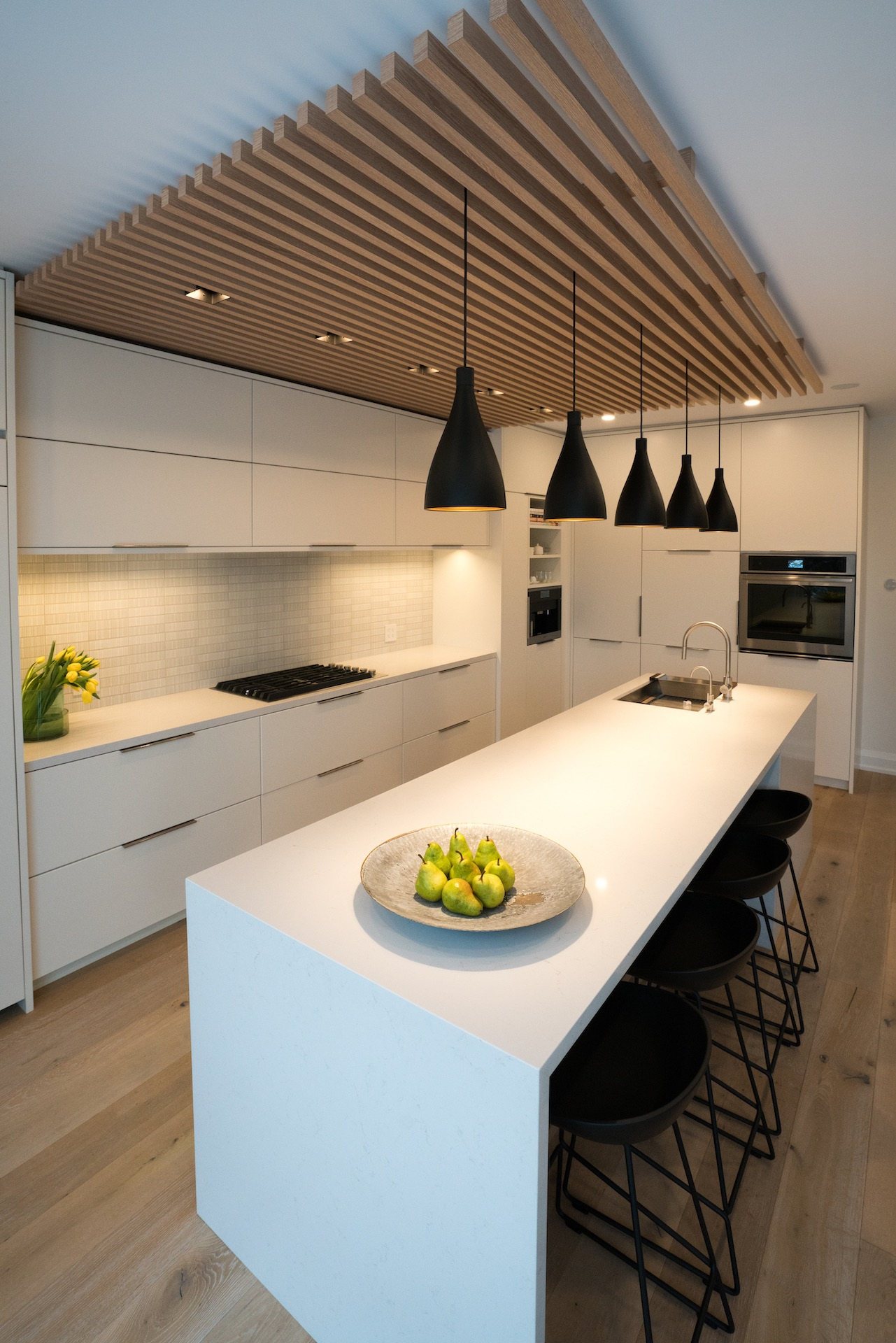 White kitchen island with wood panels on ceiling