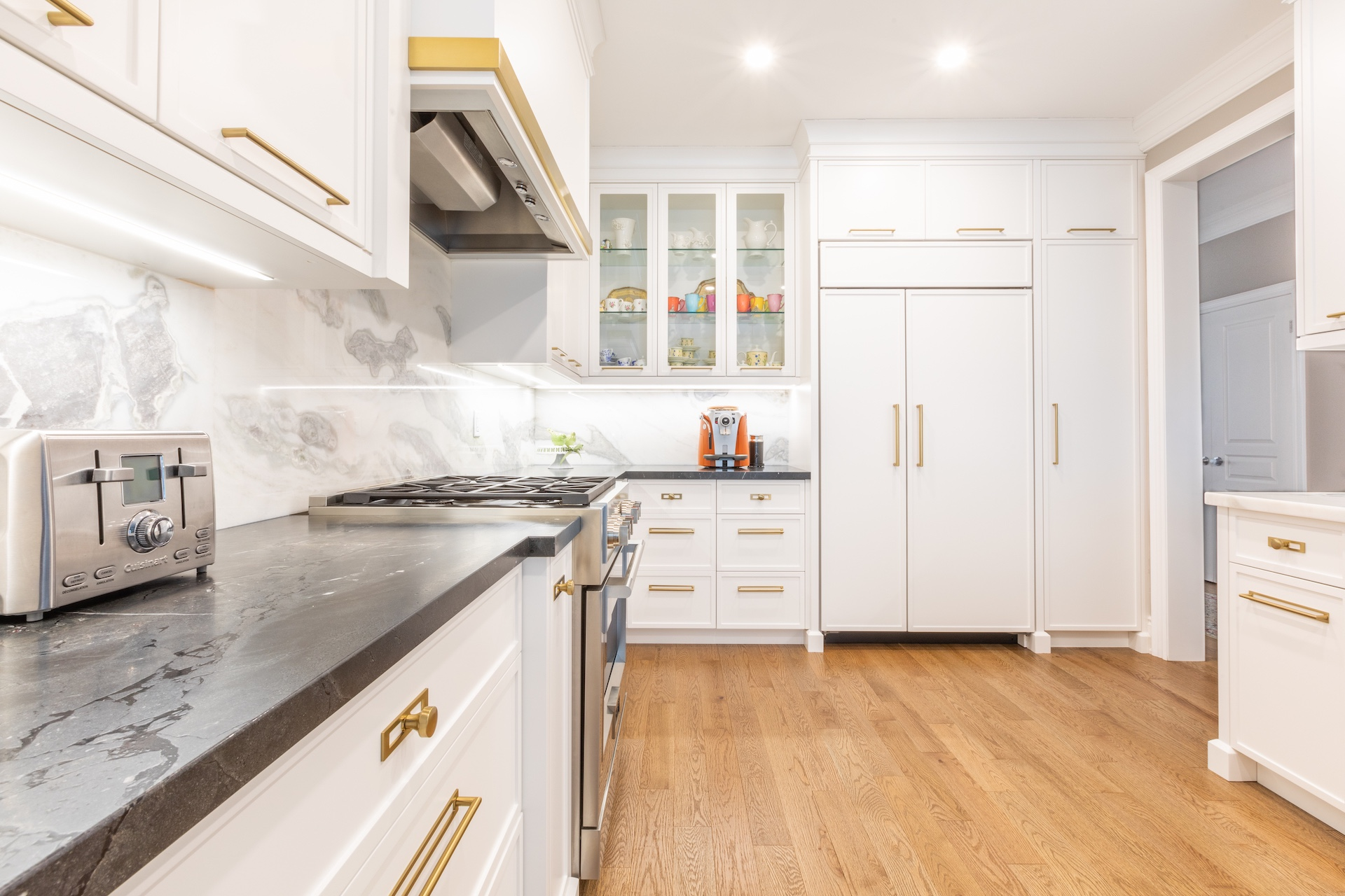 White kitchen with gold hardware and dark counters