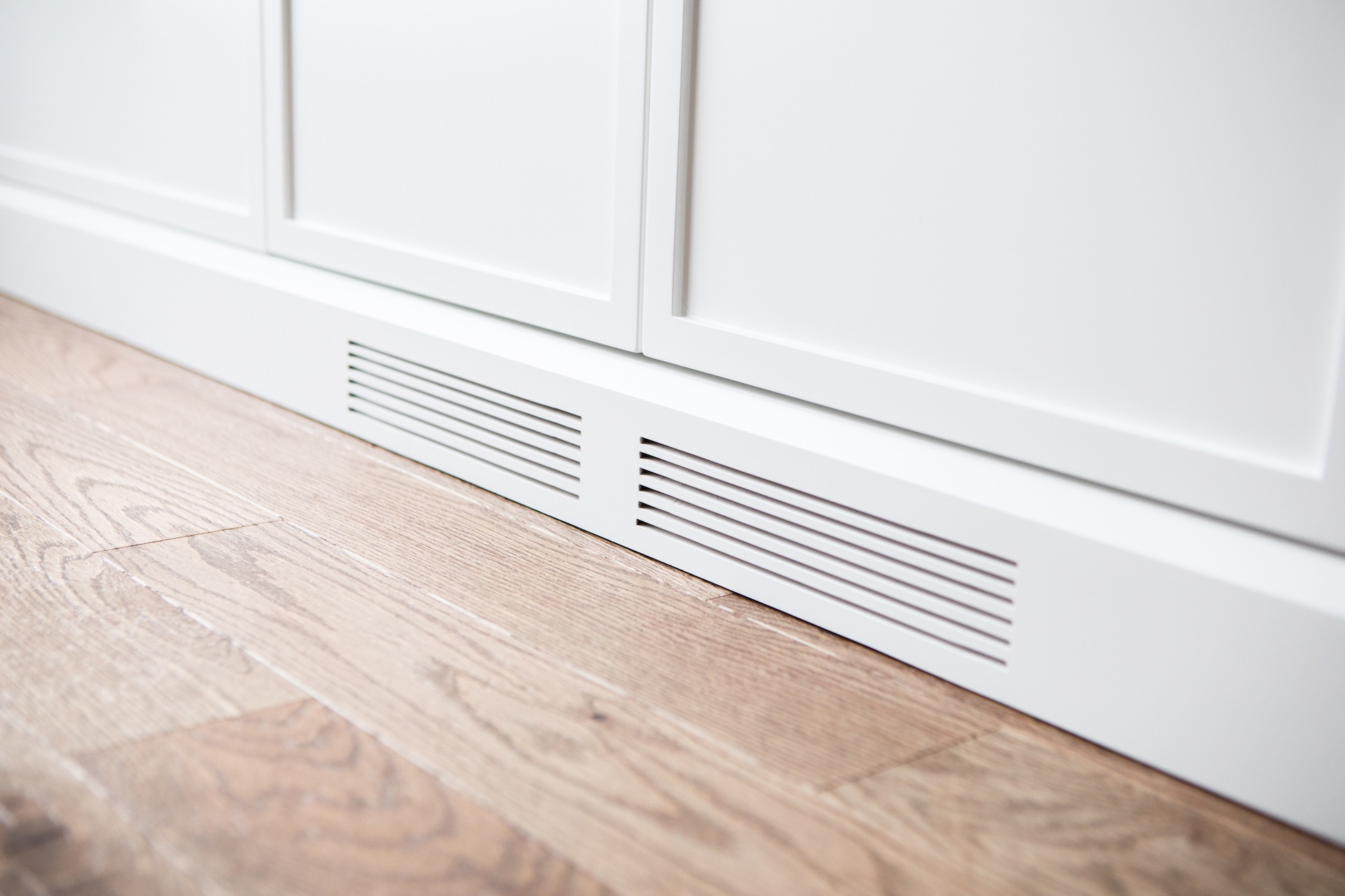 White wood baseboard and natural wood floor