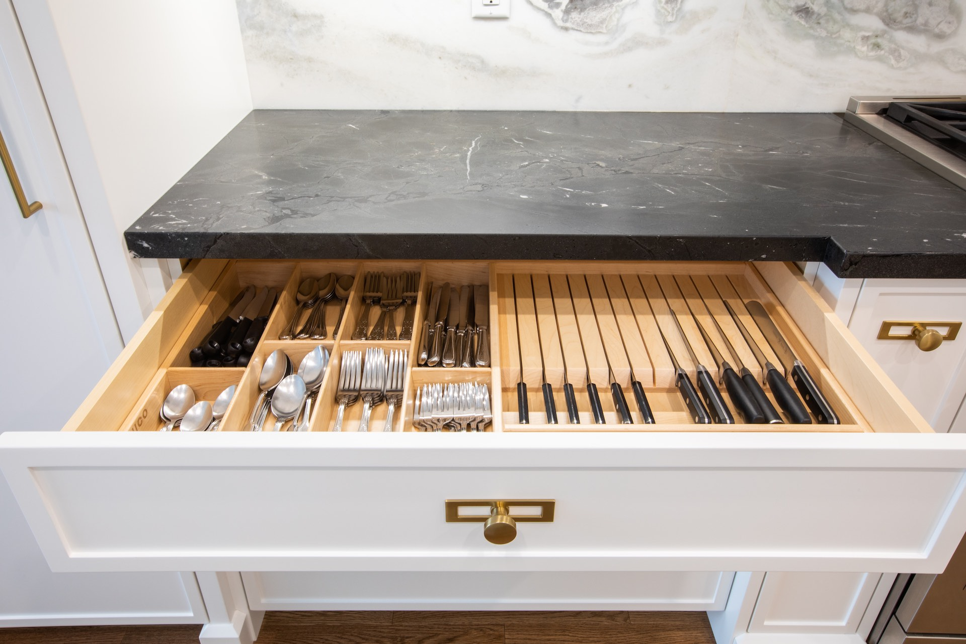 Black marble counter with white kitchen drawer open with knives