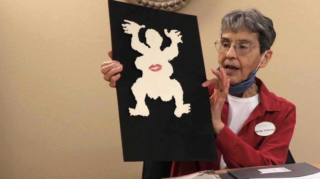Jenifer Pichinson holding up her art piece of a dancing figure in black and white.