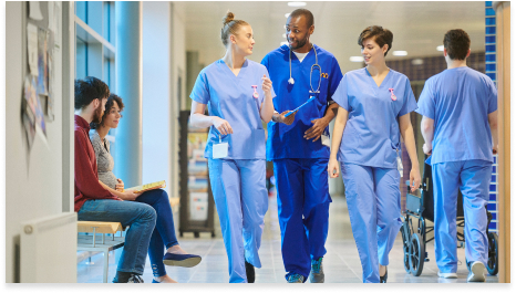 two female nurses and one male doctor walking down a hospital hallway having a conversation