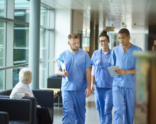 two male nurses and one female nurse walking down a corridor discussing a patient while looking at an ipad