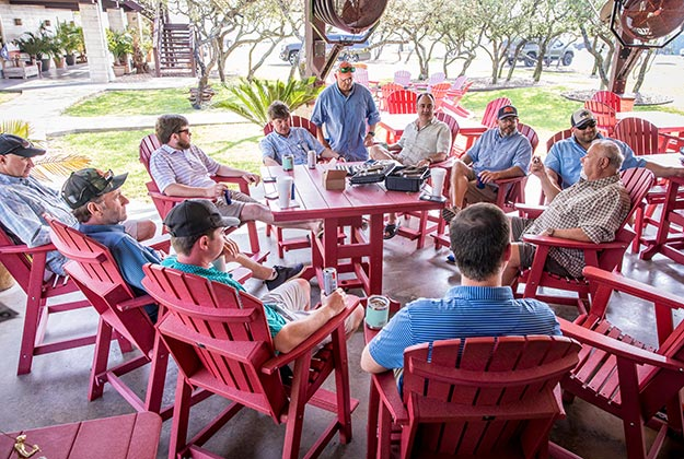 CDE Team at an outdoor function sitting on a porch in red chairs