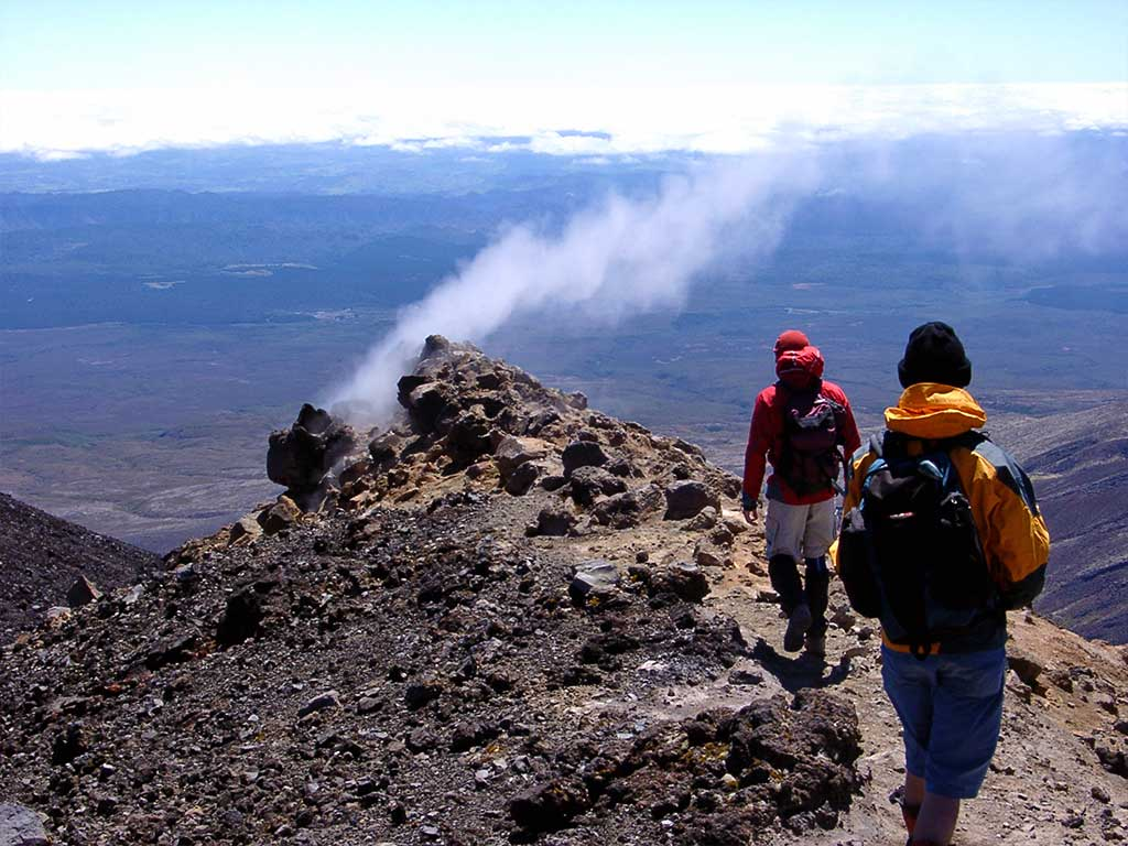 A bunch of geologists walking over geothermal rock