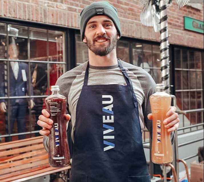 a man with a beard hold 2 viveau bottles wearing a viveau apron
