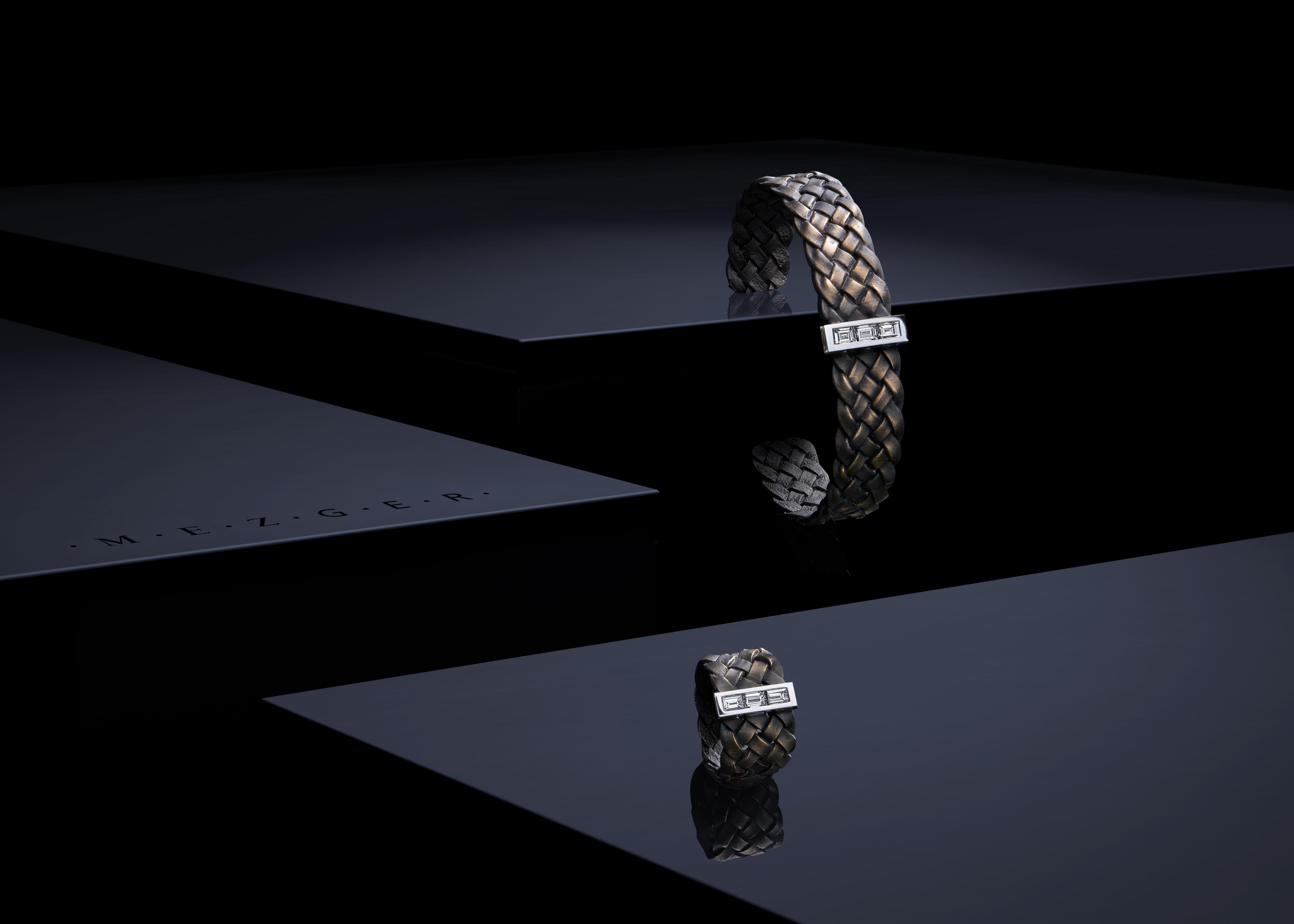 assortiment de bracelets brossé en or posé sur une surface noire brillante