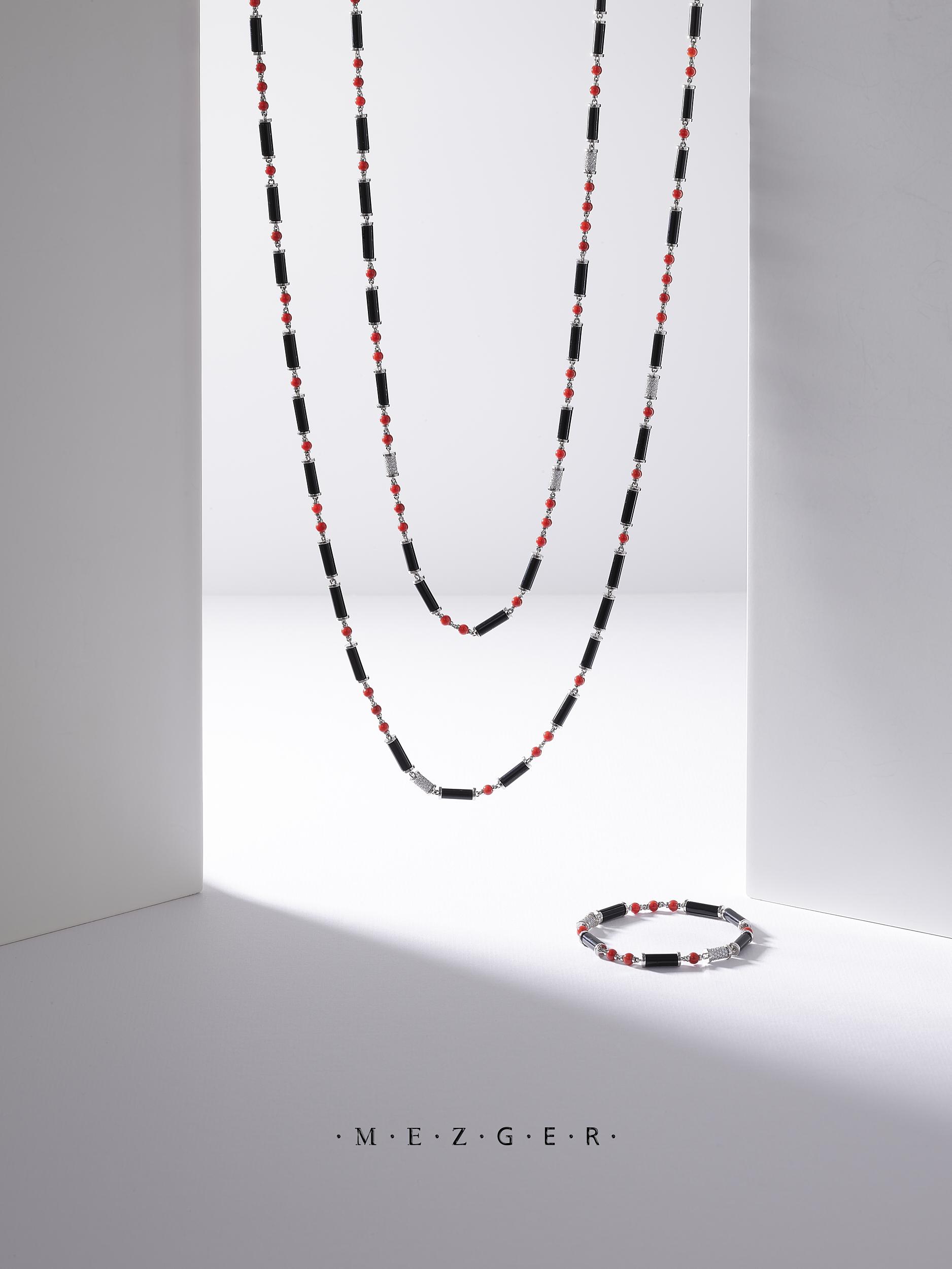 Photographie still life d'un sautoir et d'un bracelet en corail , onyx noir et diamants. Création du Joaillier Bijoutier Mezger à Basel Suisse