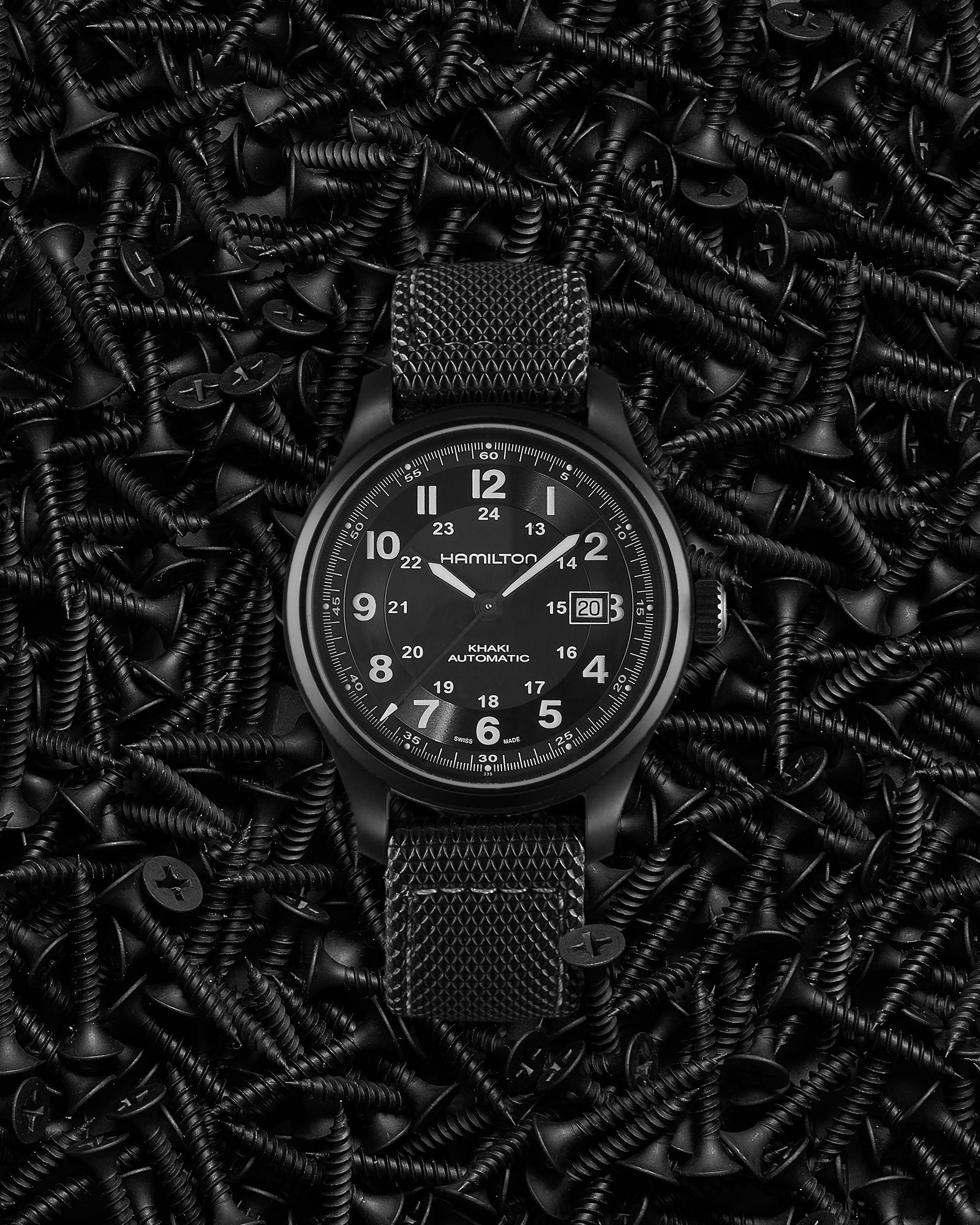 photo still life de la montre hamilton sur un fond décor de vis noires