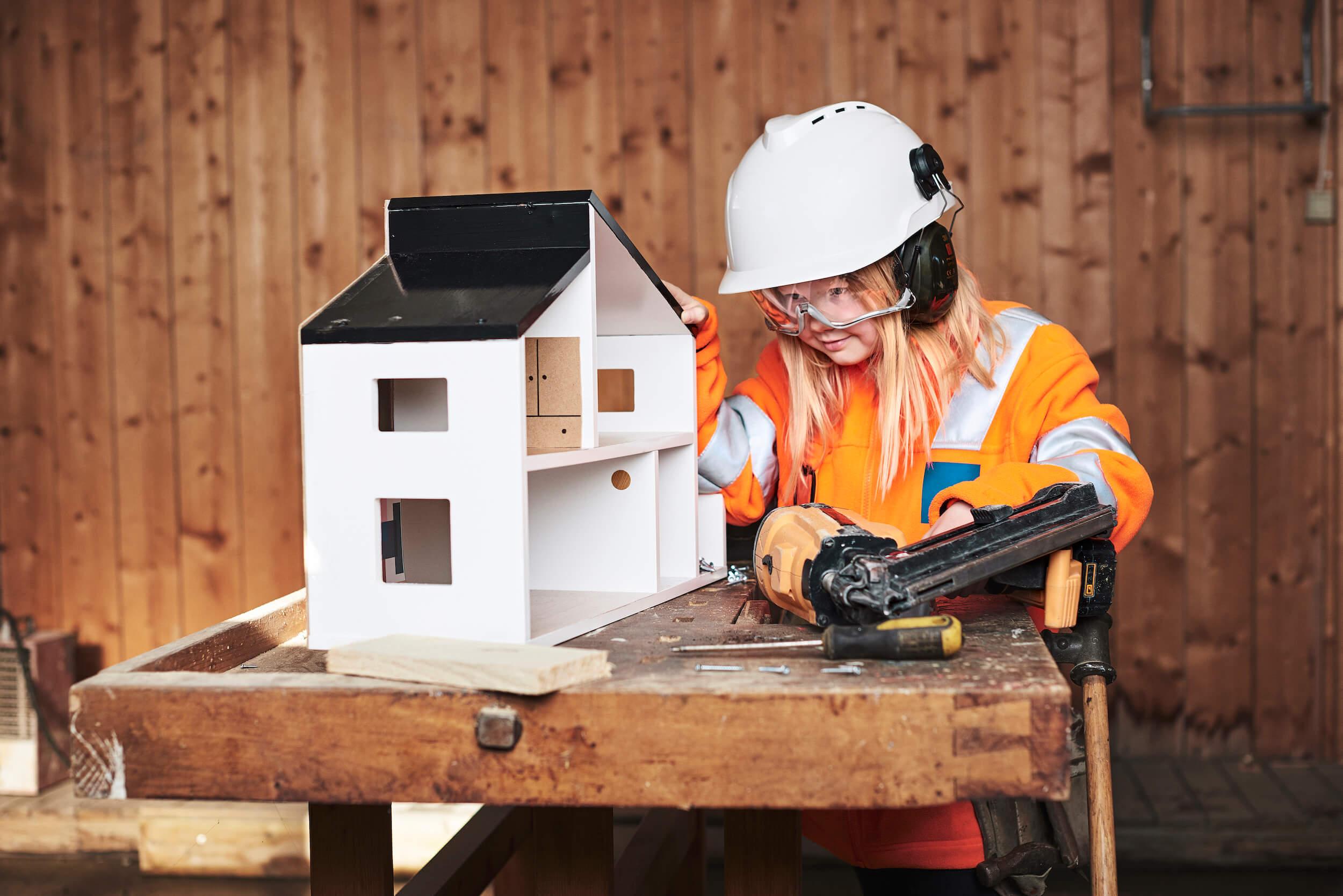 Jente med arbeidsklær leker med å bygge et lite trehus