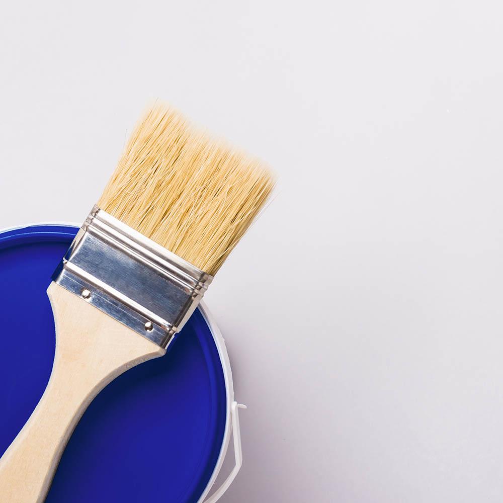 Blå målarfärg och pensel