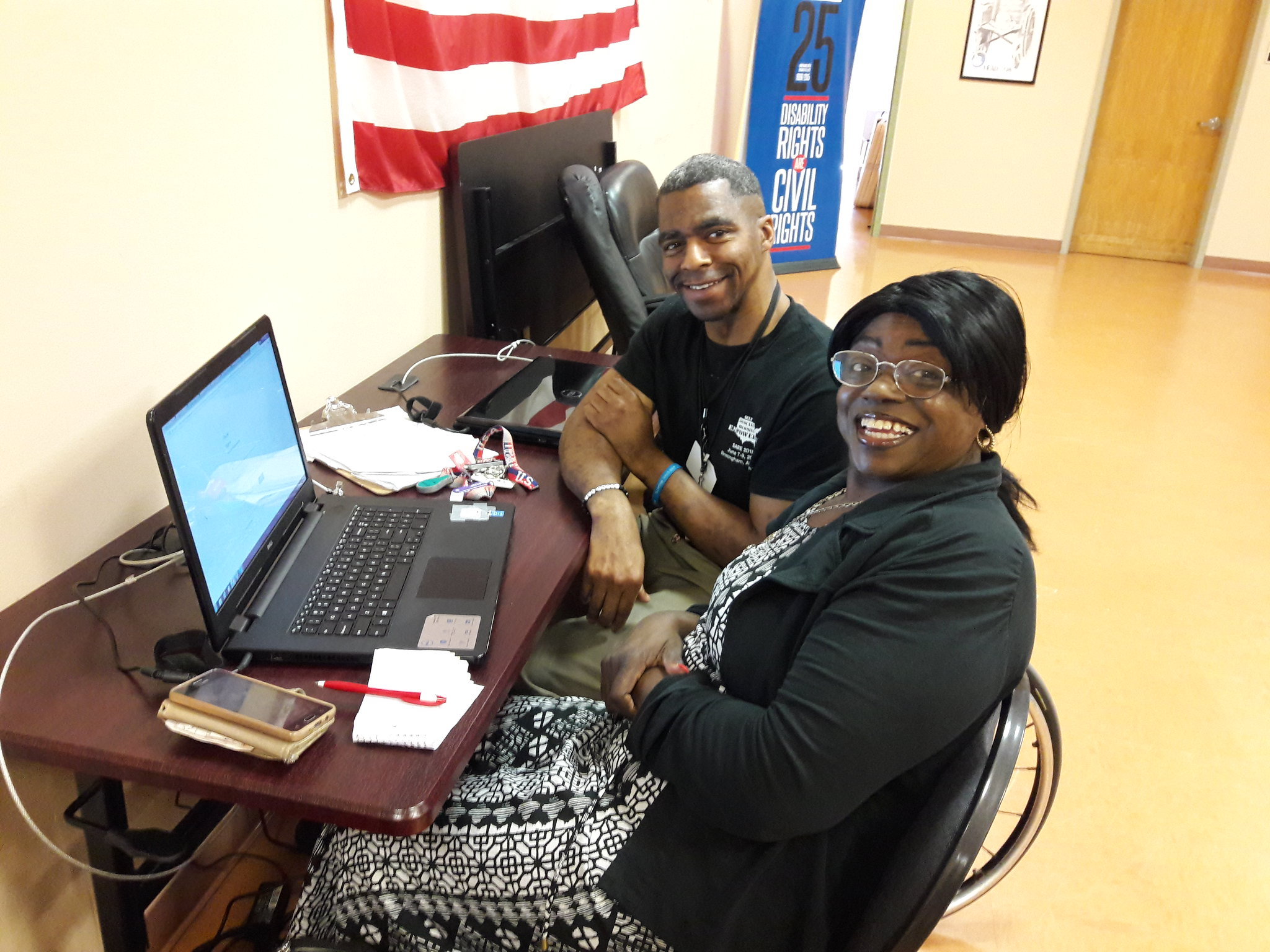 Two smiling people sit at a desk. One uses a wheelchair