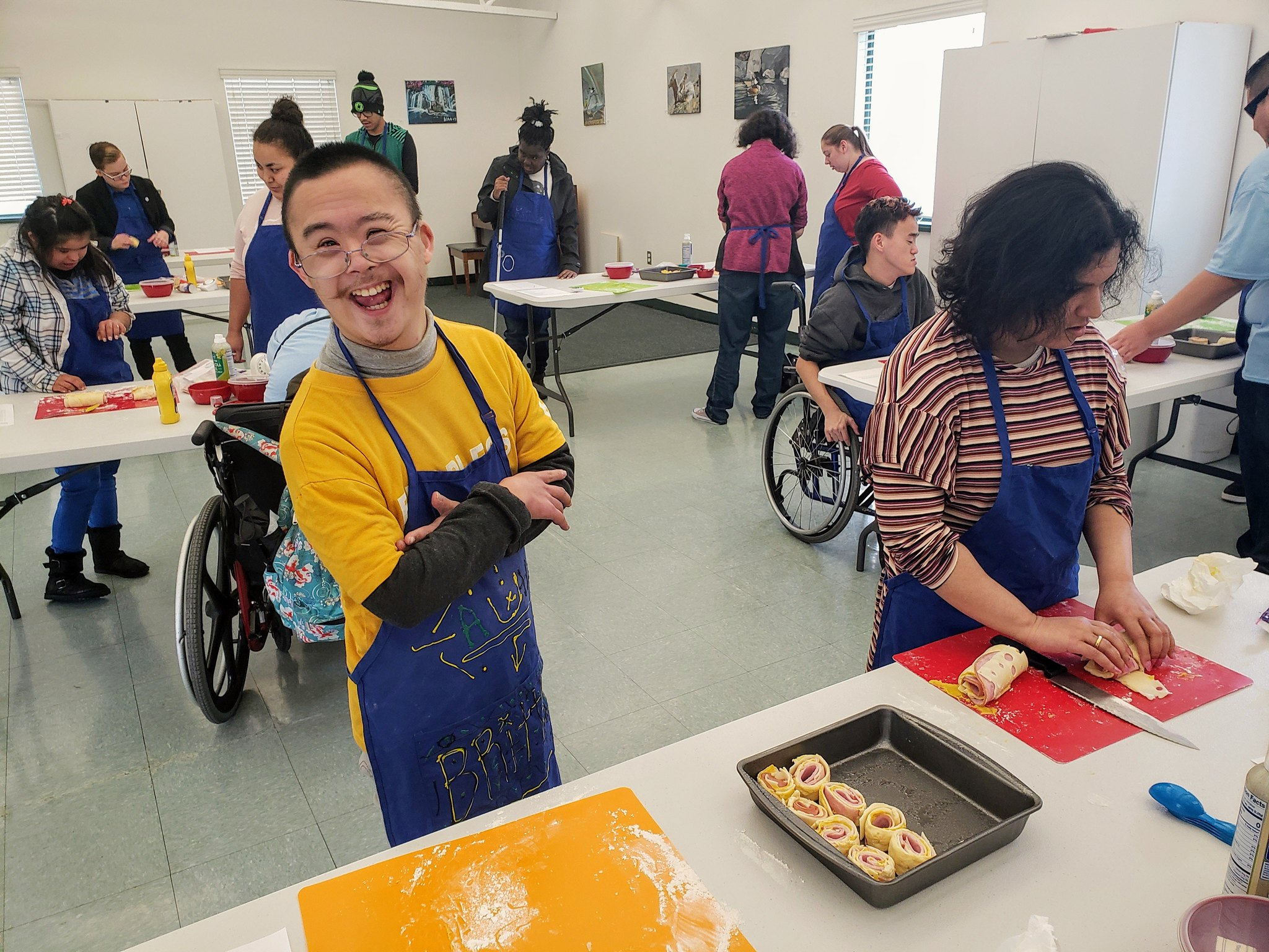 Youth with Down Syndrome smiles as he participates in cooking class