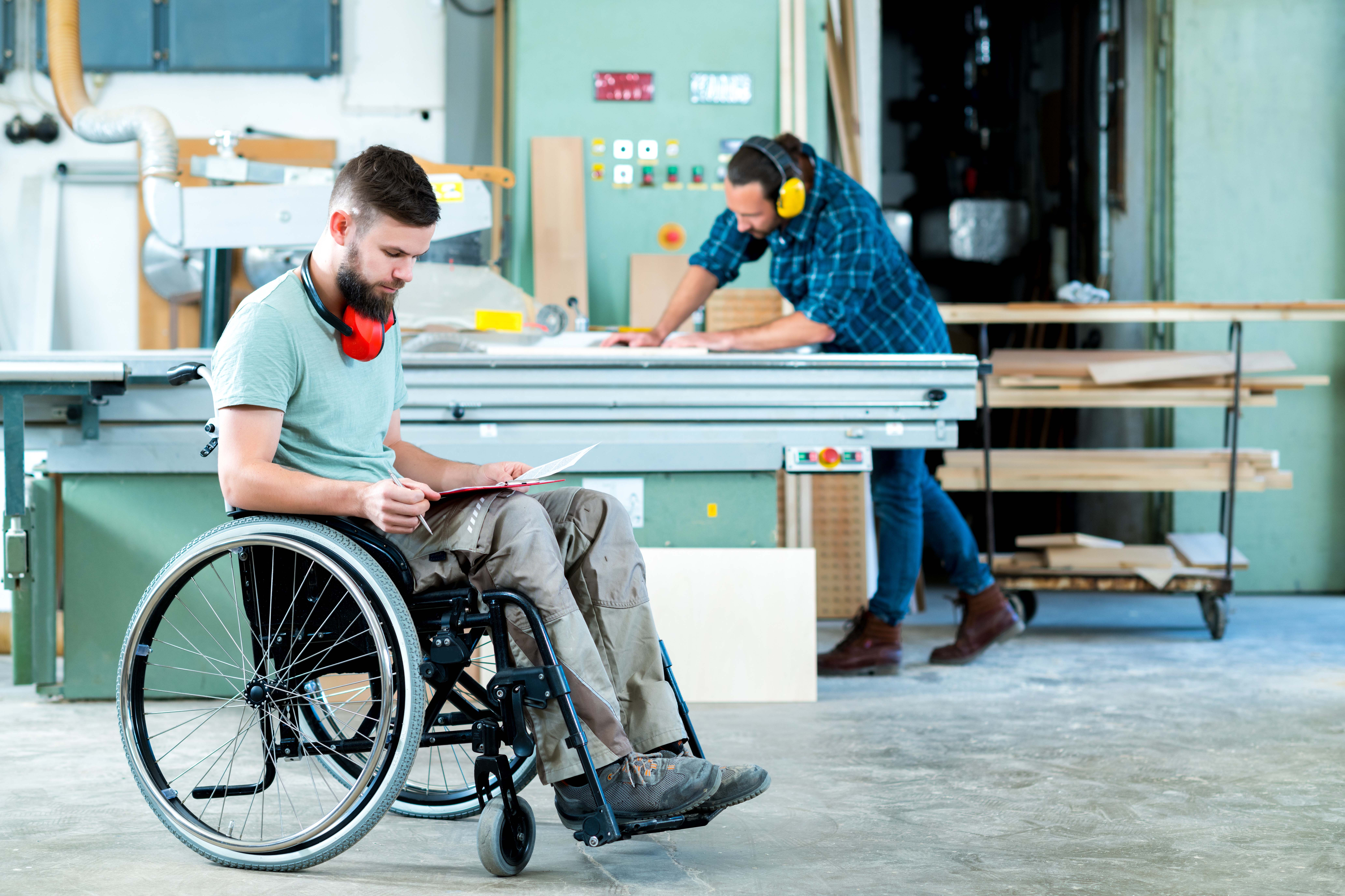 Wheelchair-using carpenter looks over building plans