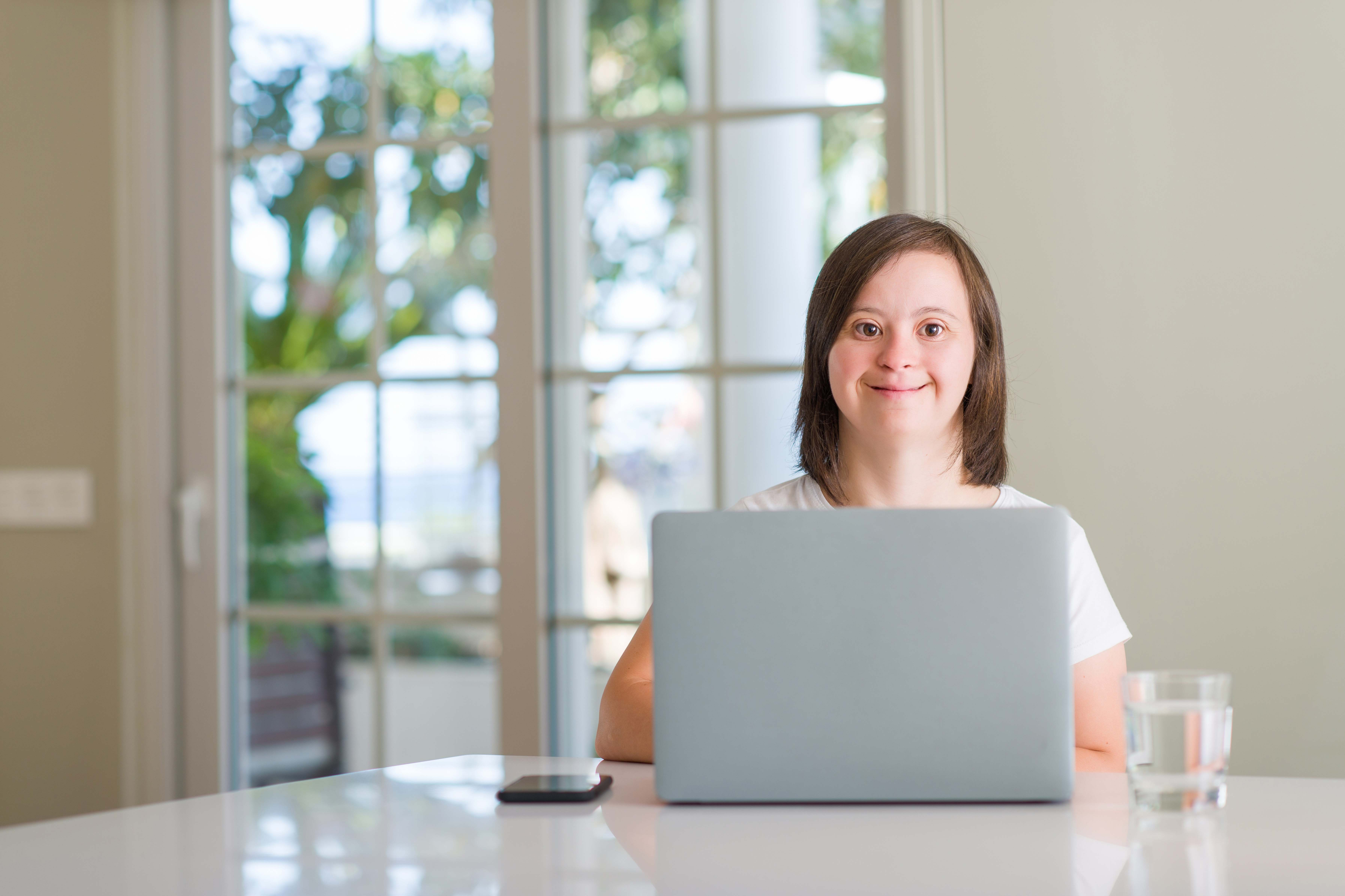woman with down syndrome smiles and uses laptop