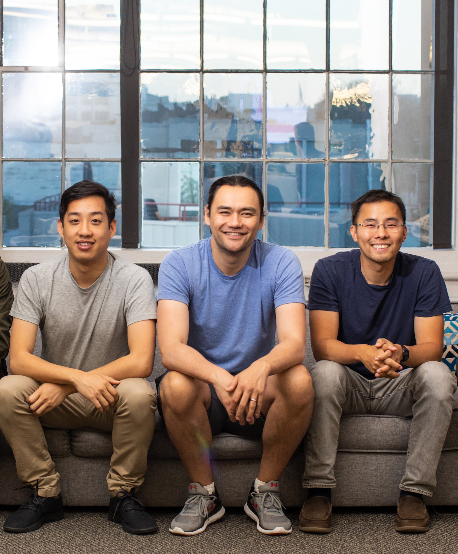 CaptivateIQ founders sitting together on a couch and smiling