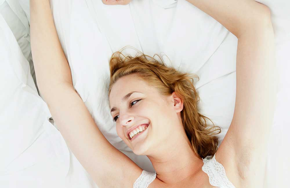 woman lying in her bed, happy