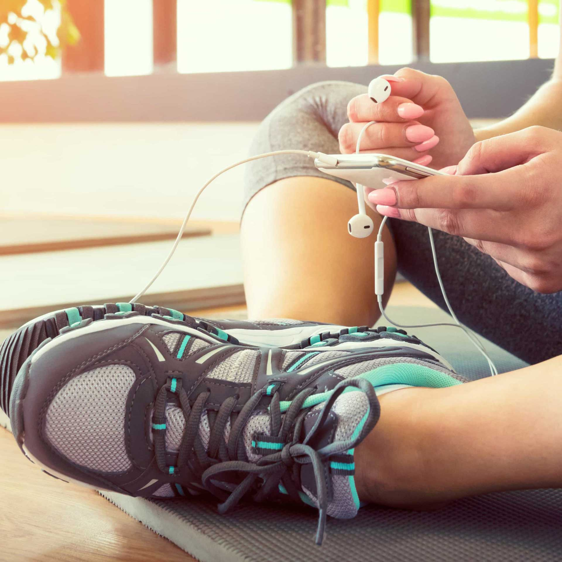Female fitness person putting on her earphones