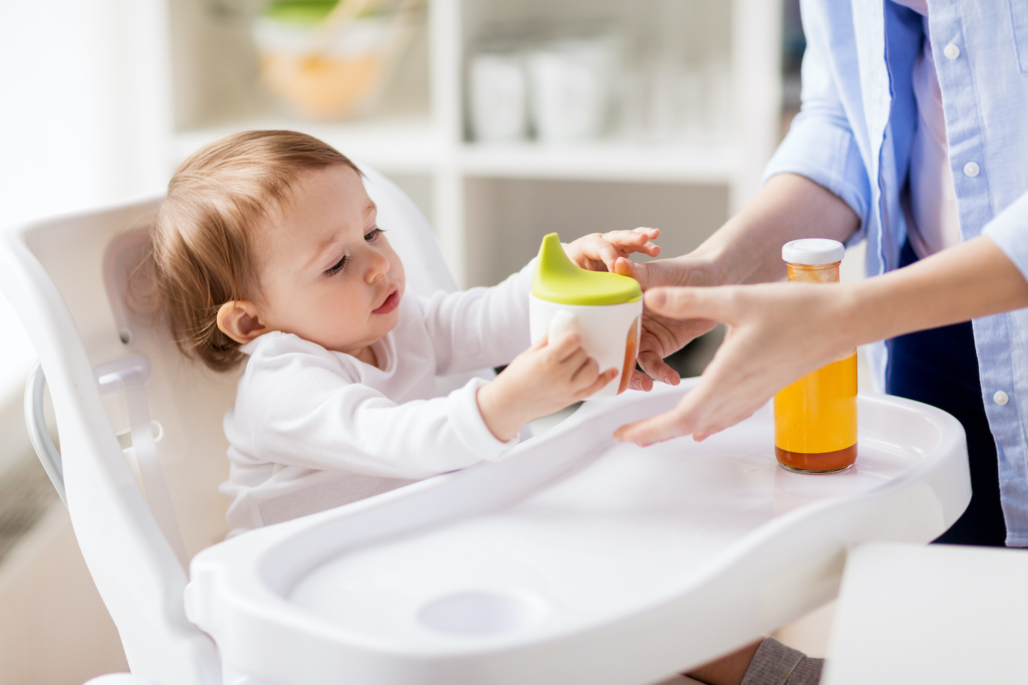 Child with sippy cup in high chair