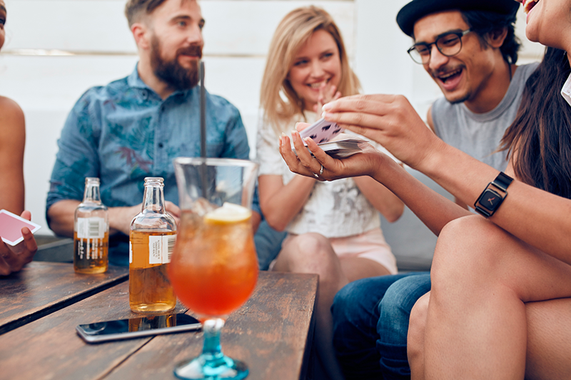 A group of people playing cards with drinks