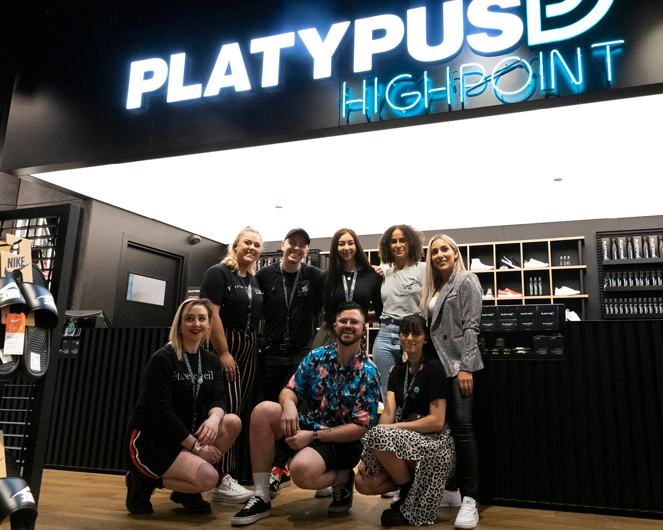 Platypus Highpoint retail team standing in front of logo sign