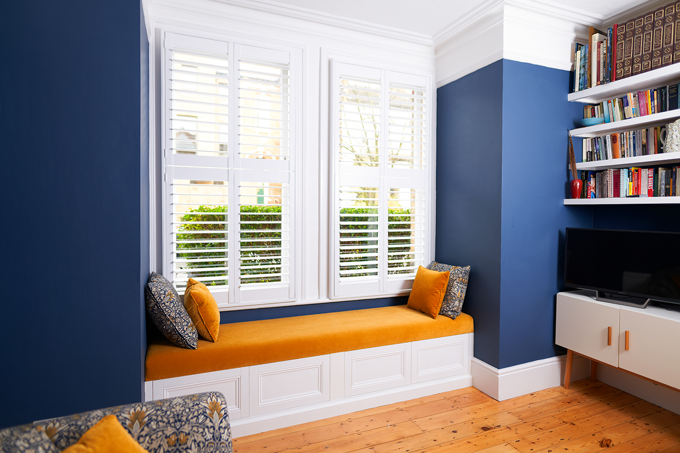 A blue alcove with orange bench