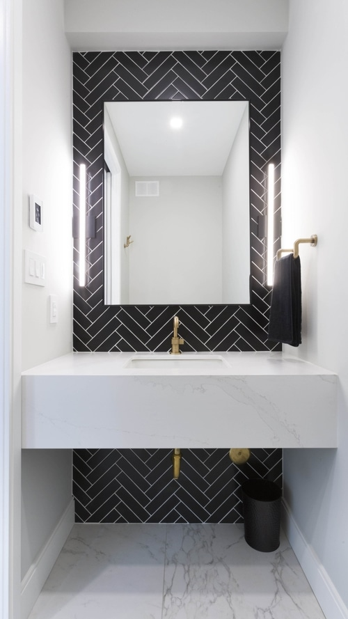 A shot of the entire powder room with the mirror, sink and floor
