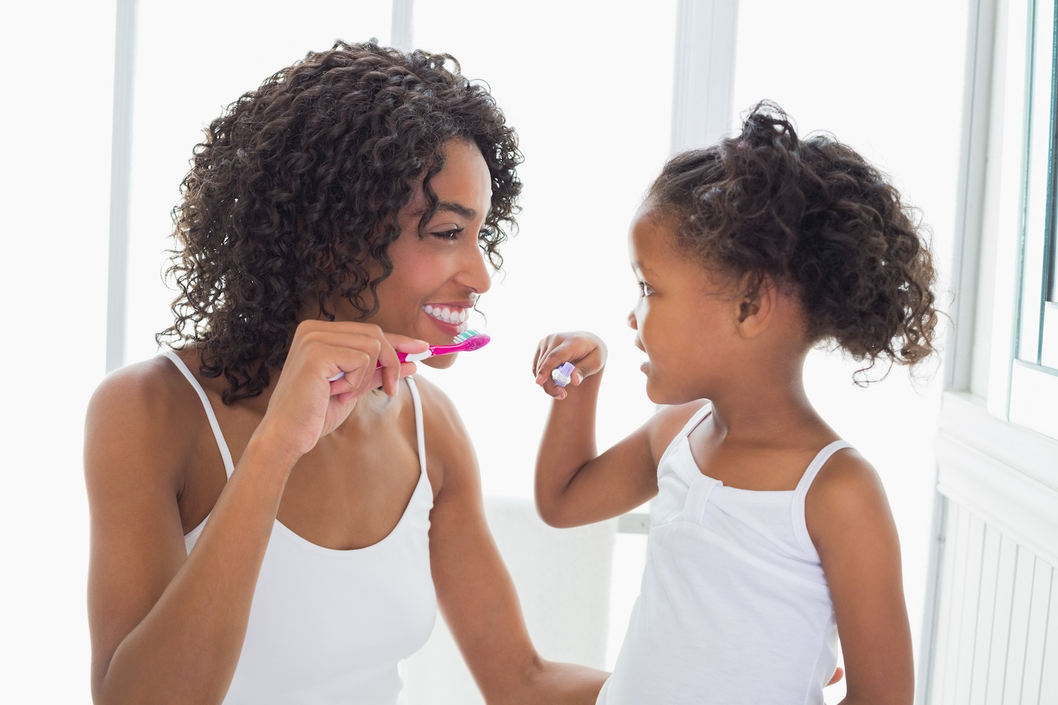 parent and child brushing teeth together
