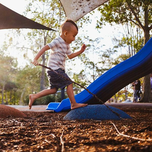 a boy running on a playground