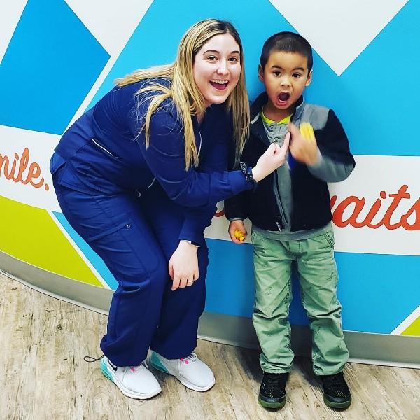 a dental hygienist and boy smiling together