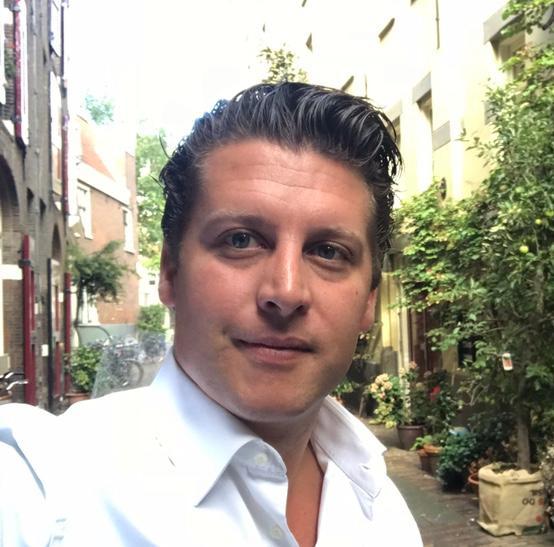 man met bruine haren en wit overhemd met struiken