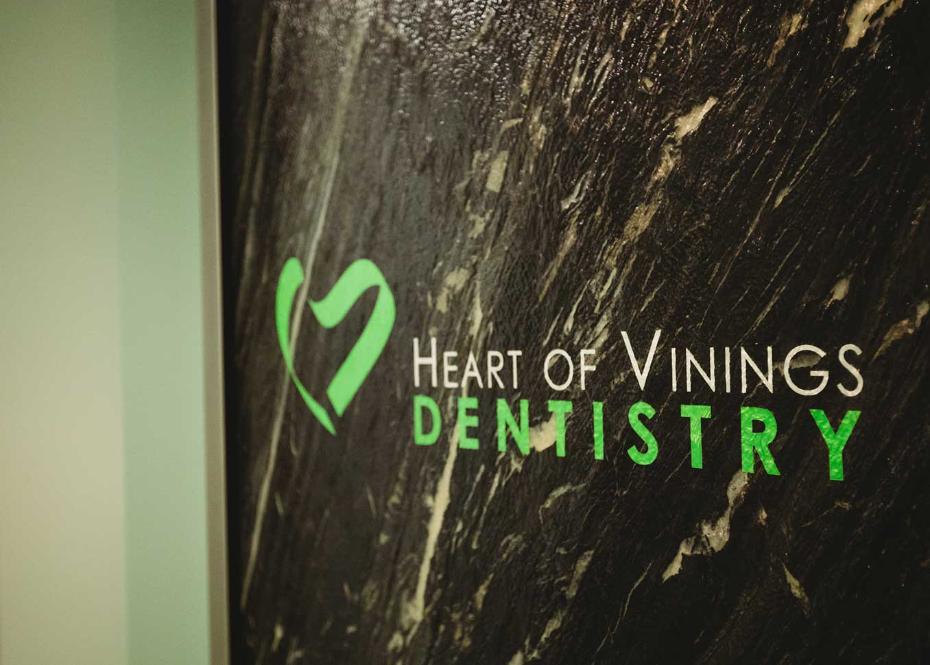 Photo of the Heart of Vinings Dentistry logo on a wall