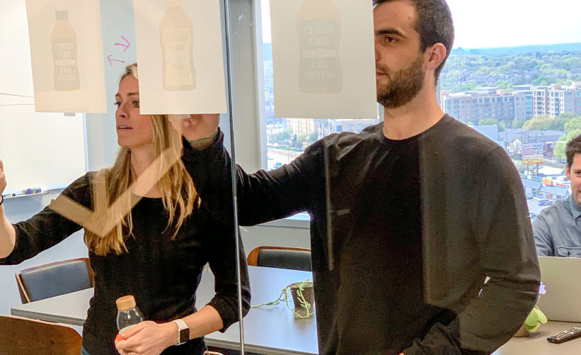 A man and a woman drawing on clear glass