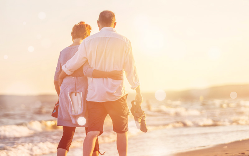 Happy retired couple walking along seafront