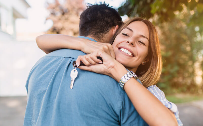 mortgage planning - smiling couple with keys to new home