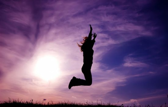 a woman jumping for joy in the air