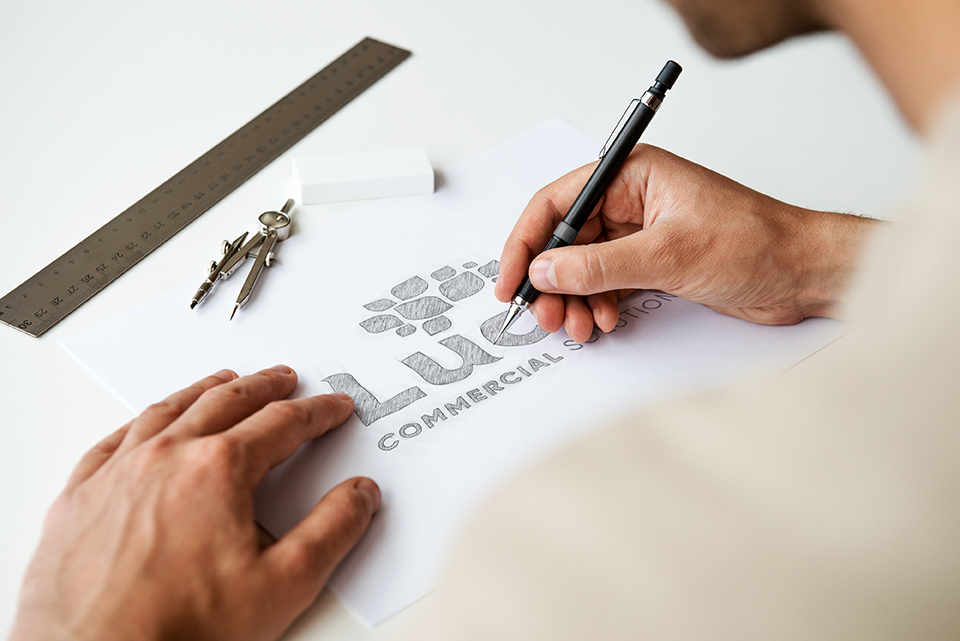 Man drawing a sketch of the Lucro Commercial Solutions logo.